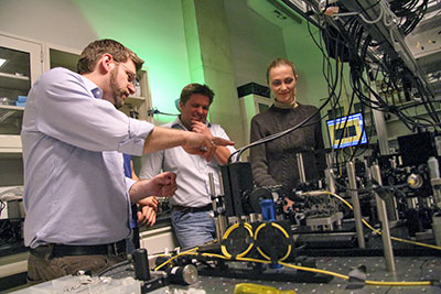 Robert Spekkens, Kevin Resch and Katja Ried examine a quantum optical circuit in the Quantum Optics and Quantum Information Lab at the University of Waterloo